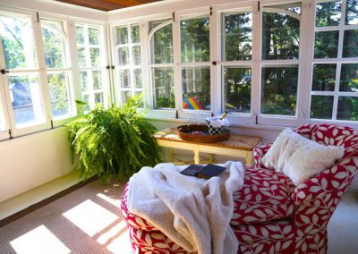 We bring in throws and pillows, live and silk plants to create a welcoming nook in this summer sleeping porch.