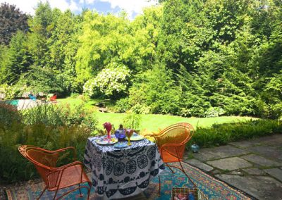 A room with a view! An outdoor carpet set on slate with a patterned tablecloth, votive candles and picnic basket create a romantic moment after work.