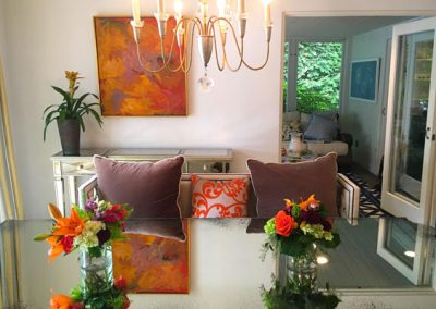 Dual bouquets of Spring flowers coordinate with the pillows and art that we have placed in this open plan dining room.