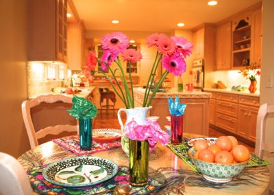 Join us for lunch! The vibrant colors of the Gerbera daisies, tangerines, reflective drinking glasses, patterned placemats and handmade ceramic plates bring joy to an otherwise neutral kitchen.
