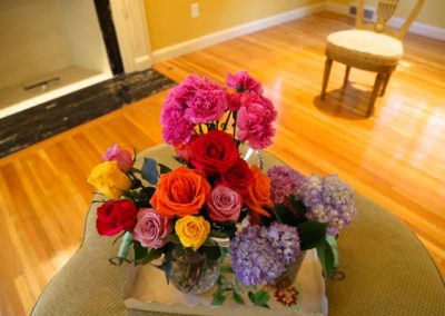 A rainbow of fresh flowers adds a splash of color to the livning room of the all brick Georgian colonial.
