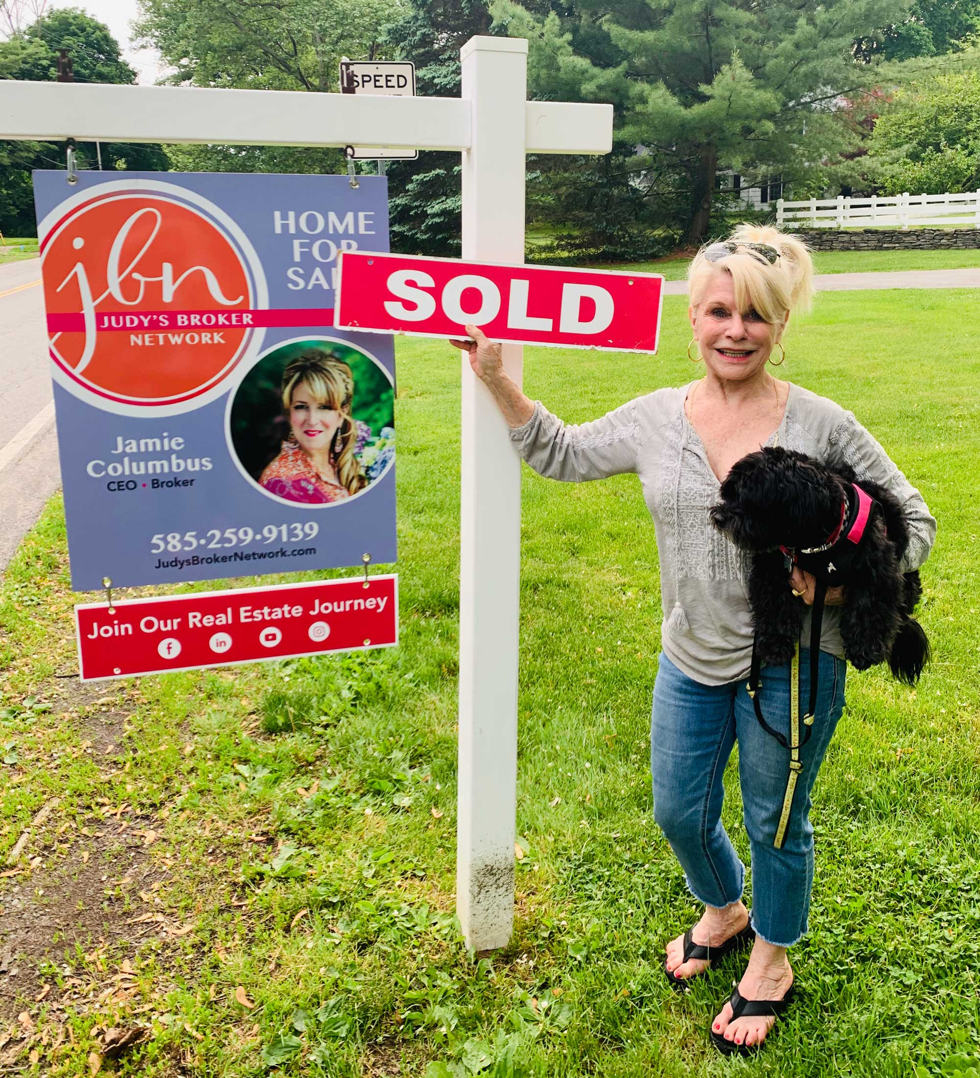 photo of homeowner with Sold sign and Judy's Broker Network sign in front of home